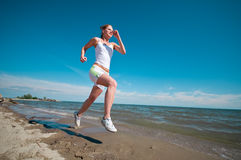 Sport woman running in sea coast Stock Photography