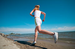 Sport woman running in sea coast Royalty Free Stock Image