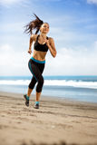 Sport woman running in sea coast on sunny day Stock Photo