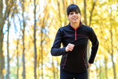 Sport woman running with trees on background Stock Photos