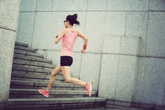 Sport woman running upstairs on city stairs Stock Photography