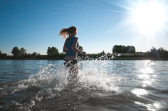 Sport woman running in water Stock Photography