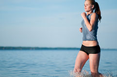 Sport woman running in water Stock Photos