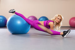 Sport woman sits on a twine. Athletic girl doing stretching exercise in the fitness room Royalty Free Stock Photos