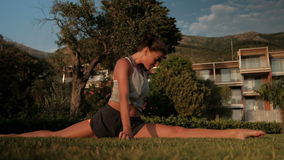 Sport woman sitting on ground on left split, stretching exercises stock video