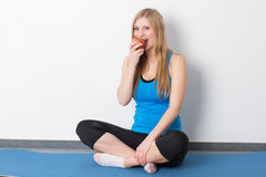 Sport woman sitting on mat with apple Stock Images