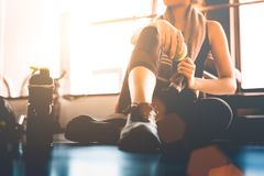Sport woman sitting and resting after workout or exercise in fit. Ness gym with protein shake or drinking water on floor. Relax concept. Strength training and royalty free stock photos