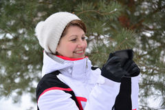 Sport woman with a smartphone in  pine winter forest Stock Photos