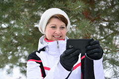 Sport woman with a smartphone in  pine winter forest Stock Images