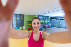 Sport woman smile at camera self picture at gym, young girl picture herself exercising fitness center Stock Image