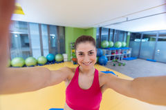 Sport woman smile at camera self picture at gym, young girl picture herself exercising fitness center Stock Images