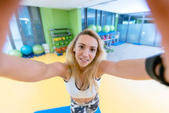 Sport woman smile at camera self picture at gym, young girl picture herself exercising fitness center Stock Photography