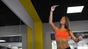 Sport woman smile at camera self picture at gym, young girl picture herself exercising fitness center. Orange top stock video footage