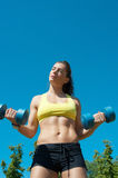 Sport woman stretching with dumbbells on playground Royalty Free Stock Photo