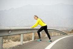 Sport woman stretching leg muscle after running workout on asphalt road with dry desert landscape in hard fitness training session Stock Photos