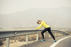 Sport woman stretching leg muscle after running workout on asphalt road with dry desert landscape in hard fitness training session. Young attractive sport woman Stock Photos