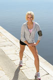 Sport woman stretching legs on a dock Royalty Free Stock Image