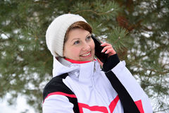 Sport woman talking on phone in  pine winter forest Royalty Free Stock Photography