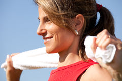 Sport woman with a towel. Woman cleaning her sweat with a towel Stock Images