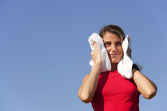 Sport woman with a towel. Woman cleaning her sweat with a towel Royalty Free Stock Photo