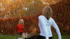 Sport woman training stretching exercise on carpet in autumn park. Yoga woman practising asana on outdoor class in city stock footage