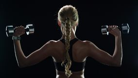 Sport woman training with dumbbells in slow motion. Fitness girl exercising