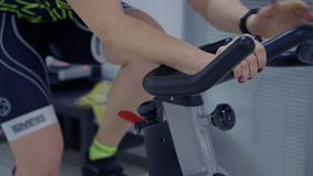 Sport woman training on exercise bike while cardio gym in fitness club. Fit woman working out on spinning bike at cycling class in sport club. Cardio vascular stock video