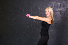 Sport woman trains her shoulders using pink dumbbells. Athletic girl holding a dumbbell pink on a black background Stock Photography