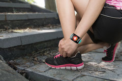 Sport woman tying shoelaces wearing health sensor smartwatch wit Royalty Free Stock Image