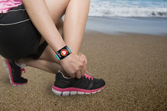Sport woman tying shoelaces wearing health sensor smartwatch wit Stock Images