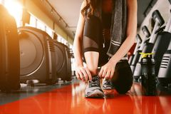 Sport woman tying sneakers rope. Sport center and Fitness gym co Stock Photo
