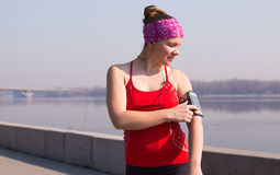 Sport woman using her phone during training outside in city quay early morning Stock Photos
