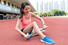 Sport woman using roller stick on legs. Asian young woman Stock Photos