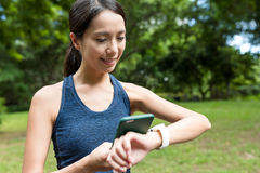 Sport woman using smart watch connect to mobile phone in the par. K ,asian young woman Royalty Free Stock Images