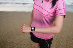 Sport woman wearing smartwatch with health sensor on beach backg Royalty Free Stock Image