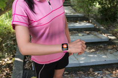 Sport woman wearing smartwatch with health sensor on forest trai Royalty Free Stock Photo