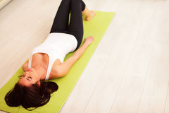 Sport woman on the yoga mat. Young woman in sport cloths lying on the yoga mat Stock Photos