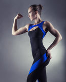Sport woman. Young athletic woman in sport overall poses for the camera against a black background Royalty Free Stock Image