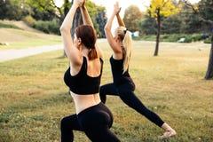 Sport women doing yoga outside in morning. Fitness girls relax in park stock images