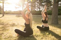 Sport women doing yoga outside in morning. Fitness girls relax in park royalty free stock photo