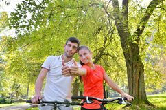 Sport women, men. Young beautiful girl and the guy on the bike, relax before driving Stock Image