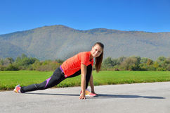 Sport women. Young pretty girl, stretch out and listen to music before running in the park Stock Images