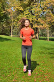 Sport women. Young pretty girl, stretch out and listen to music before running in the park Stock Photography