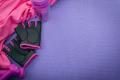 Sport, working out and bodybuilding concept with girly workout equipment like a pink pair of gym gloves, two dumbbells or weights. And a pink towel on a purple royalty free stock photos