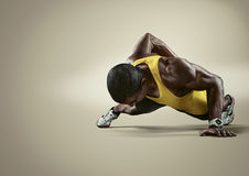 Sport. Young athletic man doing push-ups. Muscular and strong guy exercising. n stock images