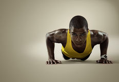 Sport. Young athletic man doing push-ups royalty free stock photography