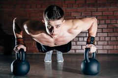 Sport. Young athletic man doing push-ups. Muscular and strong guy exercising. royalty free stock photos