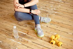 Sport young female at gym taking a break from workout and dumbbell were placed nearby. royalty free stock photos