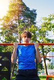 Sport. Young fit man exercising in park. Healthy lifestyle. Sport. Young fit man exercising in park. Male doing pull ups on bars. Healthy lifestyle royalty free stock photos