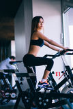 Sport young woman on a stationary bike in the gym.  Royalty Free Stock Photos